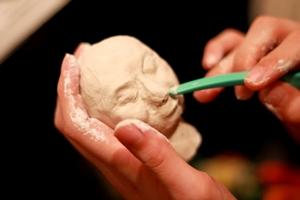 粘土で、筋肉や表情をつけていきます。